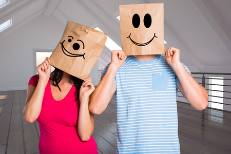 wonky: Young couple with bags over heads against white room with open door Stock Photo