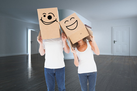 Mature couple wearing boxes over their heads against white modern room
