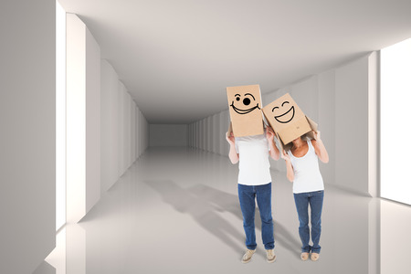 wonky: Mature couple wearing boxes over their heads against digitally generated room with bright light