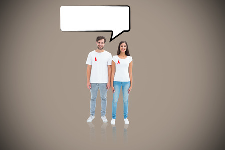 Attractive young couple wearing aids awareness ribbons against grey background with vignette photo