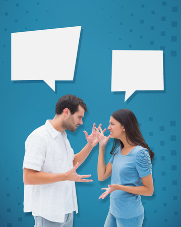 outraged: Angry brunette shouting at boyfriend against blue Stock Photo