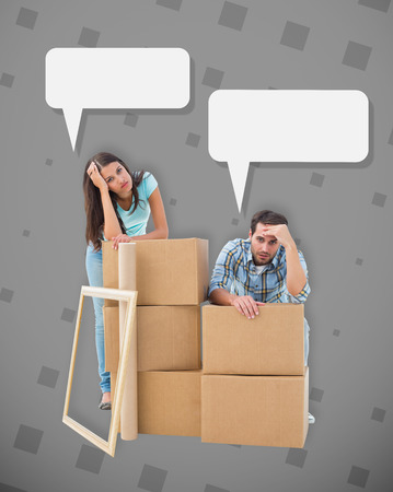 Stressed young couple with moving boxes against grey photo