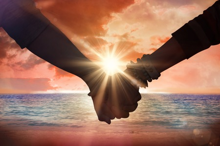 clasping: Students holding hands against sunrise over magical sea