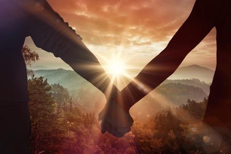 holding hands: Liebespaar mit R�ckfahr gegen Sonnenaufgang �ber Berge
