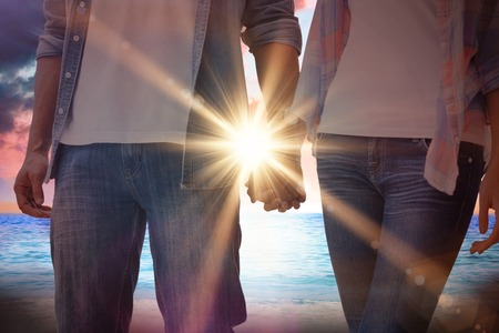 Hip young couple holding hands against sunrise over magical sea photo