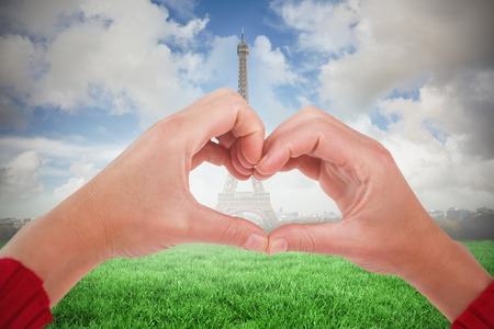 Woman making heart shape with hands against eiffel tower photo