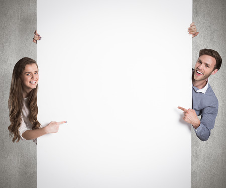 Happy young couple with blank board against weathered surface Stock Photo