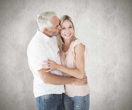cheek: Affectionate man kissing his wife on the cheek against weathered surface
