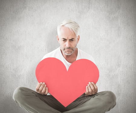 lonesomeness: Upset man sitting holding heart shape against weathered surface