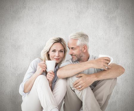 Happy couple sitting holding mugs against weathered surface photo