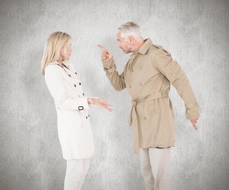 pareja enojada: Lucha contra la pareja enojado en gabardinas contra el fondo blanco