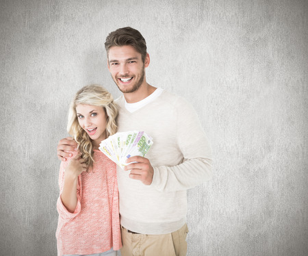 Attractive couple flashing their cash against white background photo