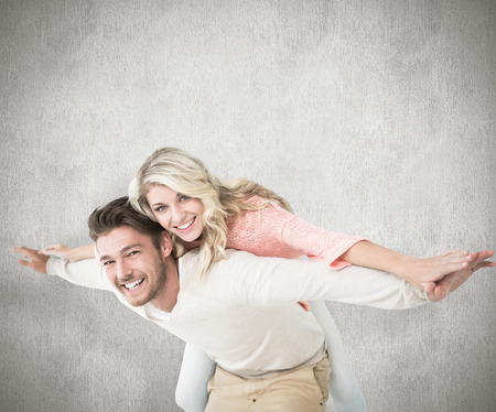 Handsome man giving piggy back to his girlfriend against white background photo