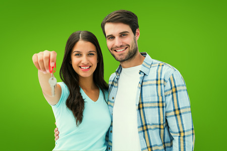 color key: Happy young couple showing new house key against green vignette