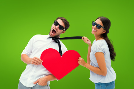 Brunette pulling her boyfriend by the tie holding heart against green vignette photo