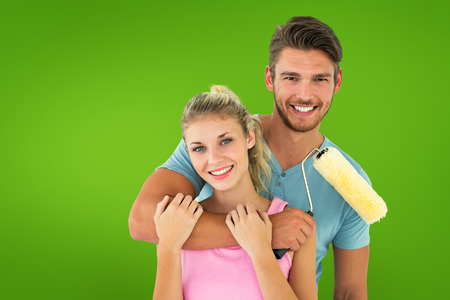 Young couple hugging and holding paint roller against green vignette photo