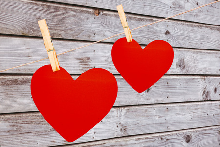 peg board: Hearts hanging on a line against digitally generated grey wooden planks Stock Photo
