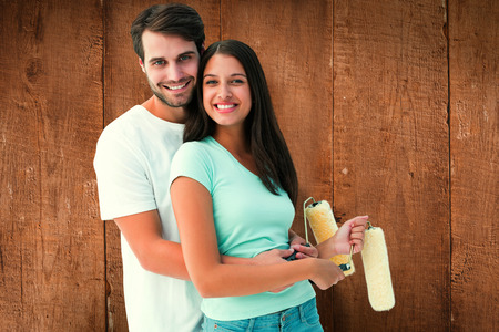 Happy young couple painting together against wooden planks photo