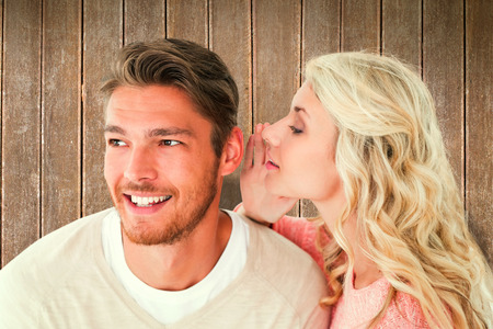 secret: Attractive blonde whispering secret to boyfriend against wooden planks