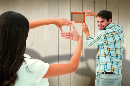 putting up: Happy young couple putting up picture frame against wooden planks Stock Photo