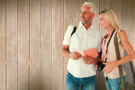 guidebook: Happy tourist couple using the guidebook against wooden planks