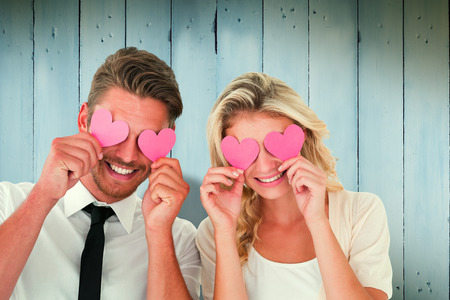 Attractive young couple holding pink hearts over eyes against wooden planks Foto de archivo