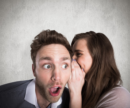 astonishment: Woman whispering secret into friends ear against weathered surface