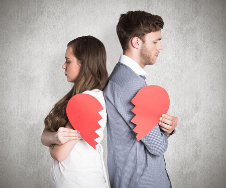 Side view of young couple holding broken heart against weathered surface Banque d'images