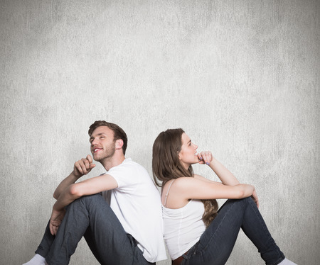 Young couple sitting on floor against weathered surface Stock Photo