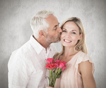 Affectionate man kissing his wife on the cheek with roses against weathered surface photo