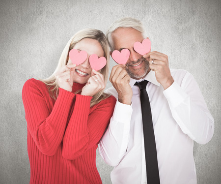 ttractive: Silly couple holding hearts over their eyes against weathered surface