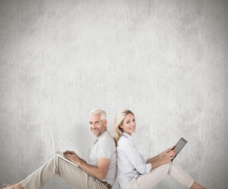 Happy couple sitting using laptop and tablet pc against weathered surface photo