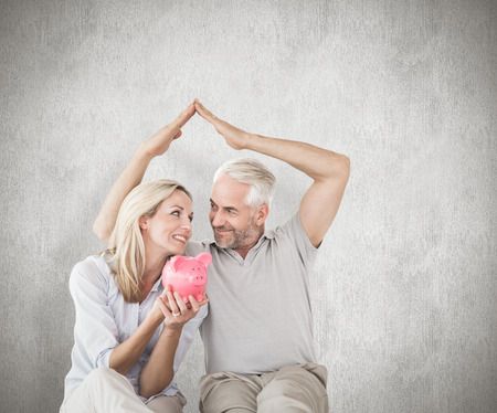 sheltering: Happy couple sitting and sheltering piggy bank against weathered surface Stock Photo