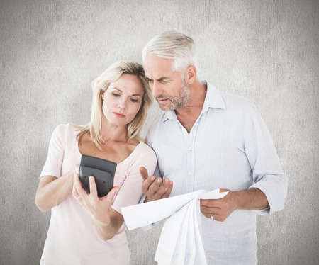 figuring: Anxious couple working out their bills against weathered surface Stock Photo