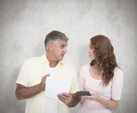 figuring: Casual couples working out their bills against white background Stock Photo