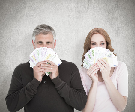 Casual couple showing their cash against white background photo