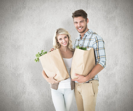 Attractive couple holding their grocery bags against white background photo