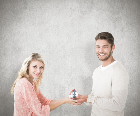 Attractive couple holding miniature house model against white background photo