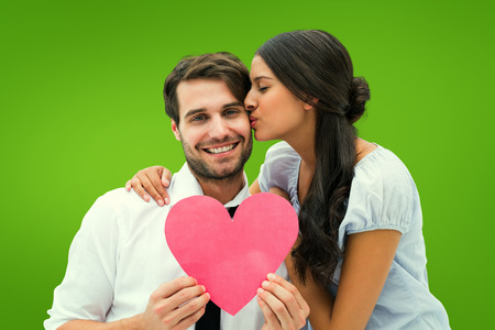 Pretty brunette giving boyfriend a kiss and her heart against green vignette