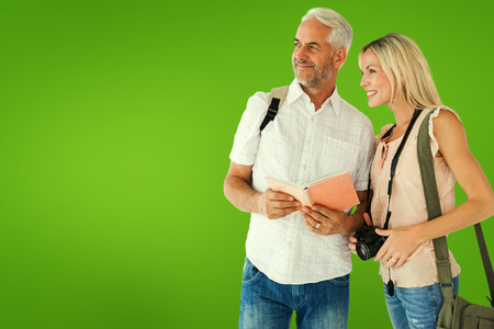 guidebook: Happy tourist couple using the guidebook against green vignette Stock Photo