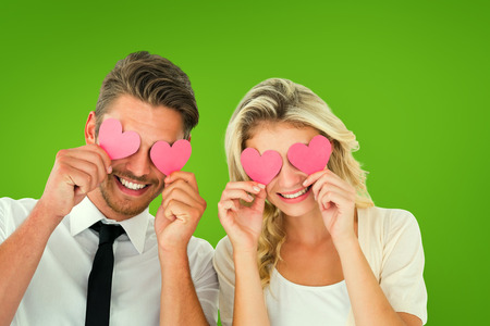 Attractive young couple holding pink hearts over eyes against green vignette