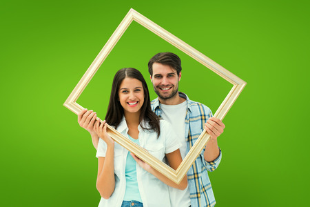 Happy young couple holding picture frame against green vignette photo