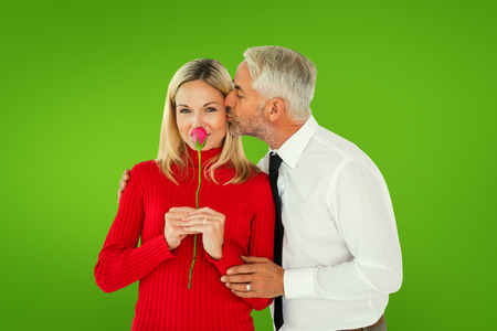Handsome man giving his wife a kiss on cheek against green vignette photo