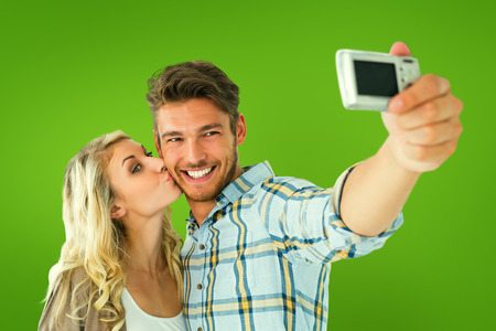 Attractive couple taking a selfie together against green vignette photo