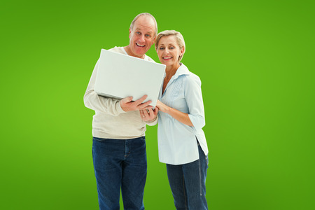 Mature couple smiling at camera with laptop against green vignette photo