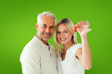 Happy couple showing their new house key against green vignette photo