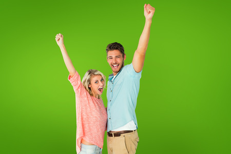 euphoria: Attractive couple smiling and cheering against green vignette