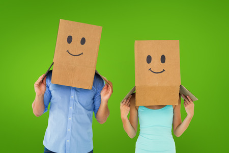 green smiley face: Couple wearing emoticon face boxes on their heads against green vignette Stock Photo