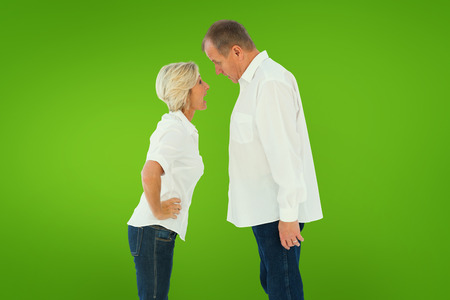 Angry older couple arguing with each other against green vignette photo