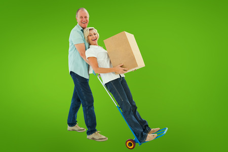 relocating: Fun older couple holding moving boxes against green vignette